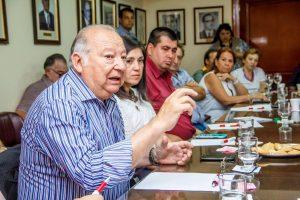 hombre hablando en una mesa de reunion
